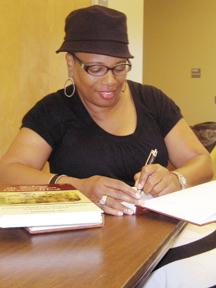 "Dr. Lauranett Lee, author of ""Making the American Dream Work: A Cultural History of African Americans in Hopewell, Virginia"" signs a copy of her book at the Juneteenth kickoff exhibit and reception Friday evening at the Appomattox Regional Library System headquarters."